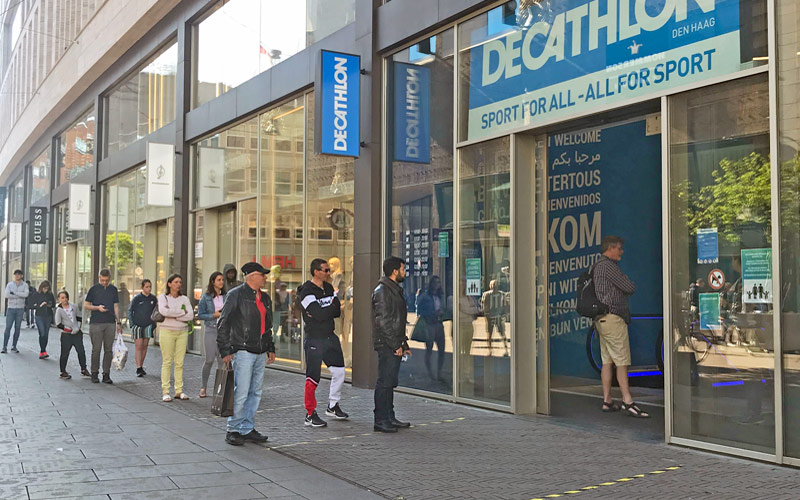 shoppers wait in line outside store in The Hague Netherlands during coronavirus